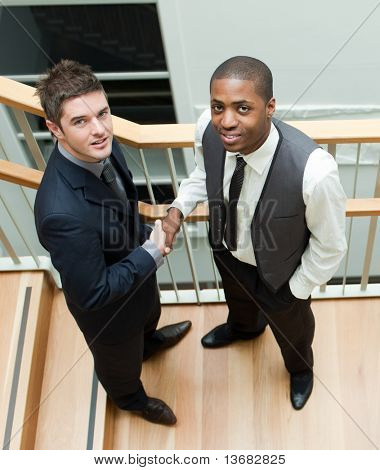 High view of Two businessmen shaking hands on stairs and smiling at the camera