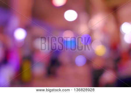 Abstract blurred image of people in night exhibition. purple light tone.