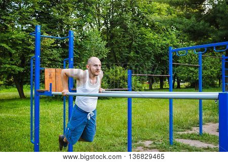 Fitness sport exercising training and lifestyle concept. Young man doing triceps dip on parallel bars outdoors