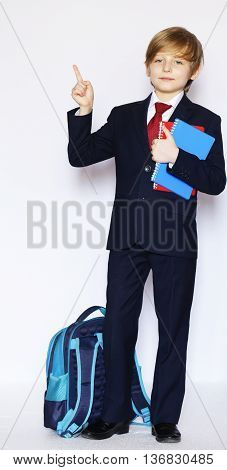 schoolboy in suit and tie with a notebook, ready to go to school