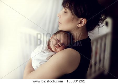 young Asian mother tenderly holds the sleeping on the shoulder of the baby in the nursery on the background of the crib