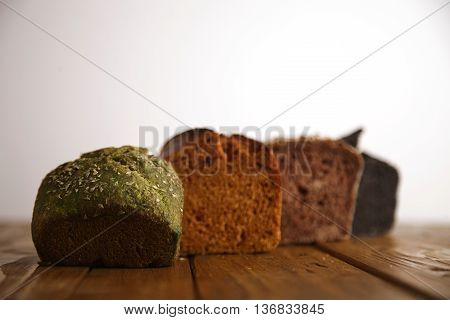 Pieces of different professional baked breads presented on wooden table as samples for sale: pistachio, dry tomato, lavender and coal. Close focus on green bread