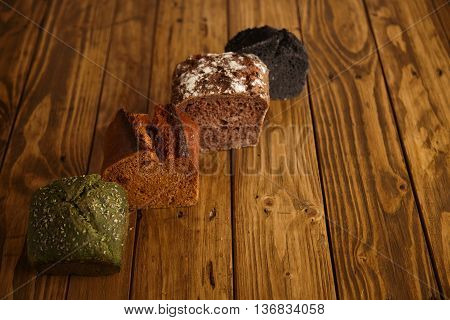 Pieces of different professional baked breads presented on vintage wooden table as samples for sale: pistachio, dried tomato, lavender and coal