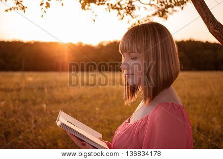 beautiful young girl reading a book close up on nature near a tree at the time of sunset the sun's rays illuminate the young girl with a book