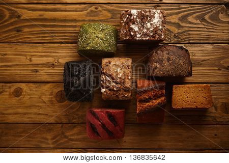 Many mixed alternative baked breads presented as samples for sale on rustic wooden table in professional bakery: pistachio, beetroot, tomatoes, lavender, sea salt, coal, sweet potato
