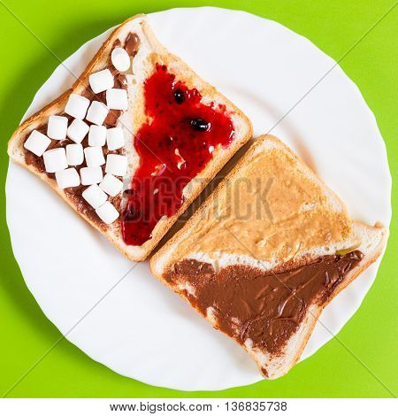 Delicious sandwich with a variety of spreads on a white plate for breakfast
