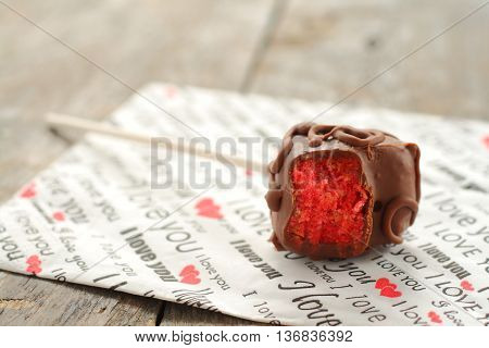Cake pops in the form of heart which took a bite is on a napkin with the words I love you