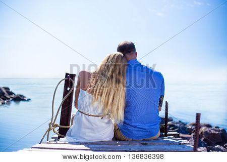 Back View Of Romantic Young Couple Sitting On The Pier