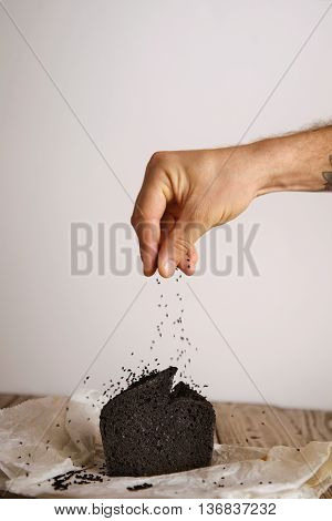 Hand pours black seeds spices on top of black coal organic homemade bread isolated on craft paper on wooden table in artisan bakery