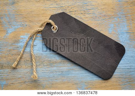 black blank paper price tag with a twine against a grunge wood