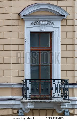 A window with an arch and balcony on the facade of the beige building. From the series window of Saint-Petersburg.