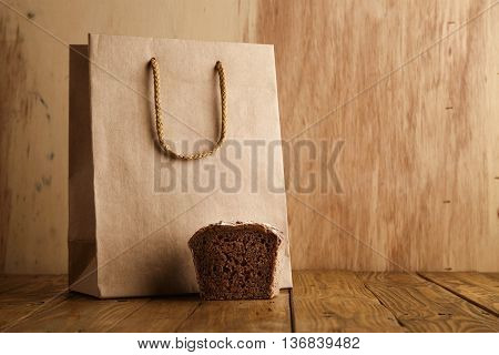 Piece of brown rye bread presented near take away blank bag from craft paper in artisan bakery on wooden background