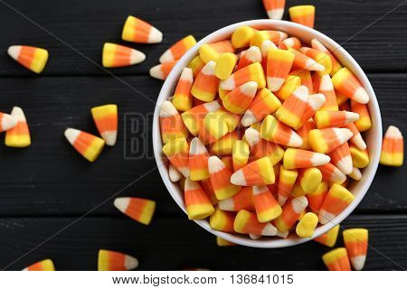 Halloween Candy Corns In Bowl On Black Wooden Background