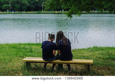 ARMAVIR, RUSSIA - JULE 02, 2016: Young women sitting on a bench by the lake and take pictures of themselves
