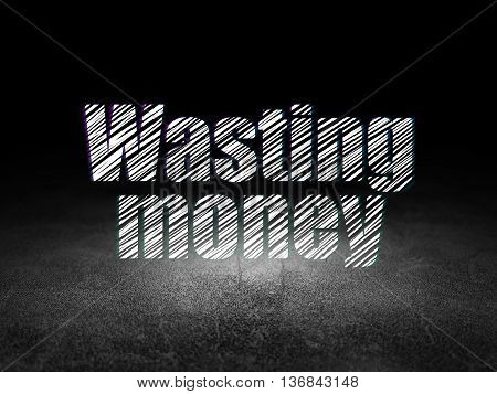 Money concept: Glowing text Wasting Money in grunge dark room with Dirty Floor, black background