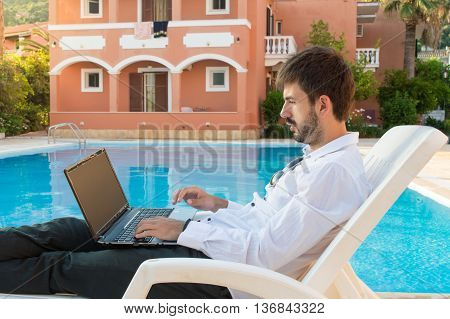 Young Bussines Man Working On His Lap Top By The Pool