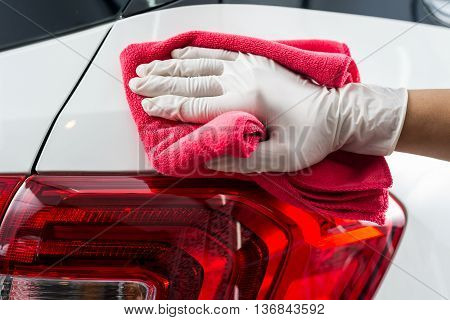 Car detailing series : Closeup of hand cleaning white car paint