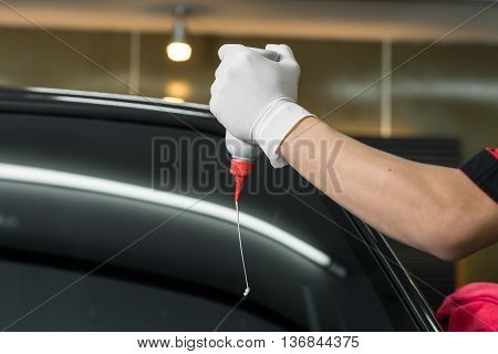 Car detailing series : Closeup of hand squeezing liquid wax on windshield