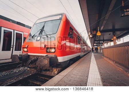 Beautiful red commuter train at railroad platform in the evening. Railway station at sunset in Nuremberg Germany