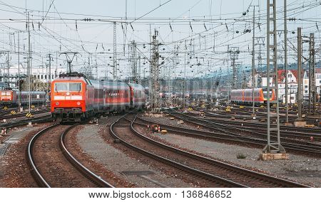 Railway Station With Modern Red Commuter Train At Sunset