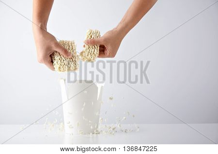 Hands break pressed pack of dry noodles above opened blank takeaway box before preparation. Commercial retail promo set mockup