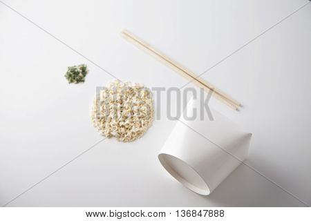 Commercial retail set of takeaway noodles business: blank closed box, dry pasta in circle shape, chopstiks and spices isolated on white side view mockup