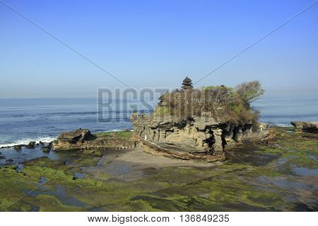 Tanah Lot Bali Indonesia during low tide and with sunrise scenery.