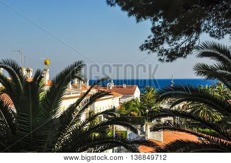Typical mediterranean resort town. Chalets near the sea. View through the trees. Travel destination. Costa Dorada Spain. Horizontal.