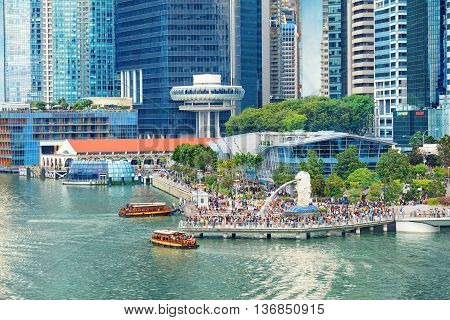 Singapore, Republic of Singapore - May 7, 2016: Crowds of tourists admire the view of Marina Bay from the pier near Merlion fountain sculpture