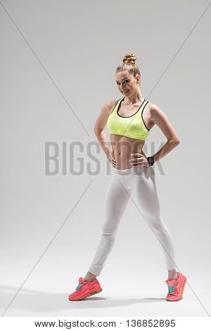 Beautiful young woman is exercising with joy. She is standing and posing with arms akimbo. The athlete is looking at camera and smiling. Isolated
