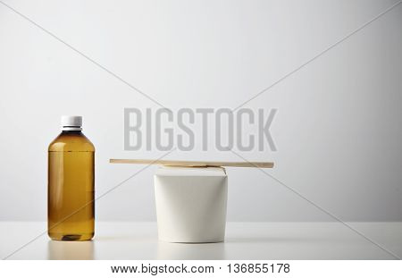 Retail takeaway presentation business set: plastic brown bottle with water on left side of closed blank noodles box with wok noodles inside and chopsticks on top isolated on white