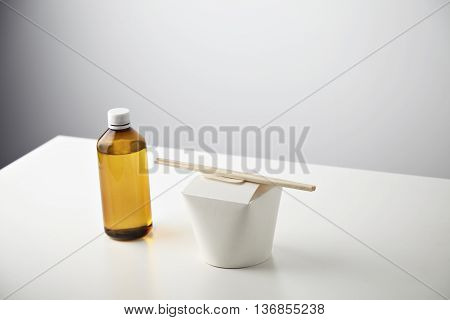 Retail takeaway commercial set: plastic brown bottle with tasty beverage on left side of closed blank wok box with wok noodles inside and chopsticks on top isolated on white