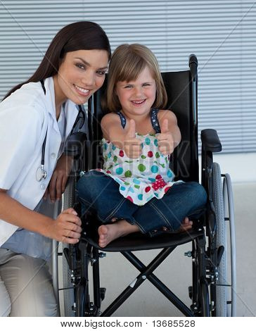 Portrait of a little girl on a wheelchair with her doctor smiling at the camera