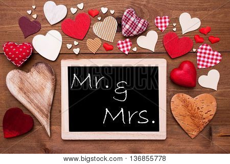 Chalkboard With English Text Mr And Mrs. Many Red Textile Hearts. Wooden Background With Vintage, Rustic Or Retro Style.
