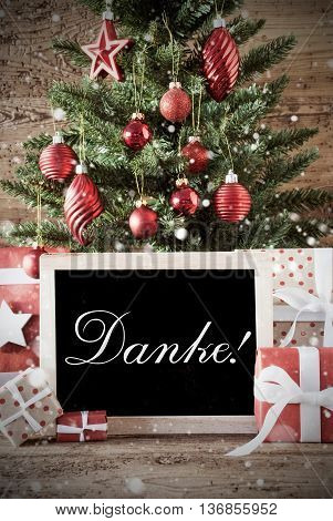 Nostalgic Christmas Card For Seasons Greetings. Christmas Tree With Balls. Gifts Or Presents In The Front Of Wooden Background. Chalkboard With German Text Danke Means Thank You