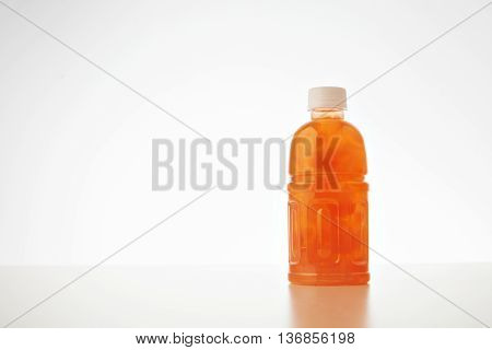 One takeaway bottle with drink from coconut cream and milk mixed with fruits and berries isolated on white Healthy refreshment sweet drink with peach bites inside.