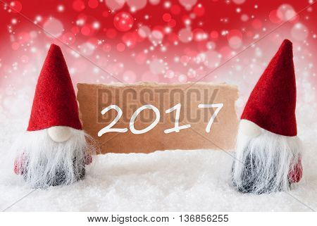 Christmas Greeting Card With Two Red Gnomes. Sparkling Bokeh And Christmassy Background With Snow. Text 2017