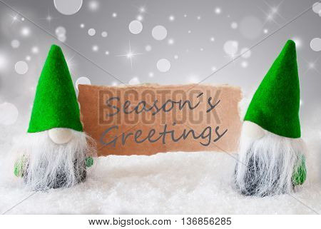 Christmas Greeting Card With Two Green Gnomes. Sparkling Bokeh And Noble Silver Background With Snow. English Text Seasons Greetings