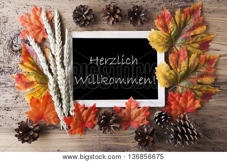 Blackboard With Autumn Or Fall Decoration. Greeting Card For Seasons Greetings. Colorful Leaves, Fir Cone And Barley On Aged Wooden Background. German Text Herzlich Willkommen Means Welcome