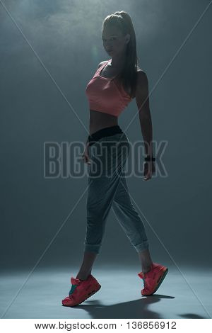 Professional female dancer is standing and posing. She is looking at camera with confidence. Smoke on background