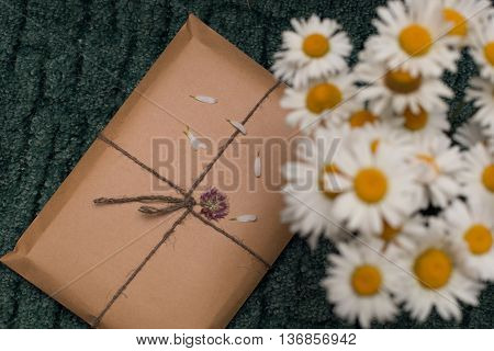 Gift packed in kraft envelope and a bouquet of daisies