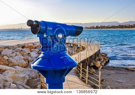 Coin operated telescope overlooking beach and seafront of maritime city with wooden bridge sea buildings and silhouette of mountains in the background. Horizontal shot.