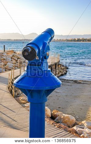 Coin operated telescope overlooking beach and seafront of maritime city with wooden bridge sea buildings and silhouette of mountains in the background. Vertical shot.