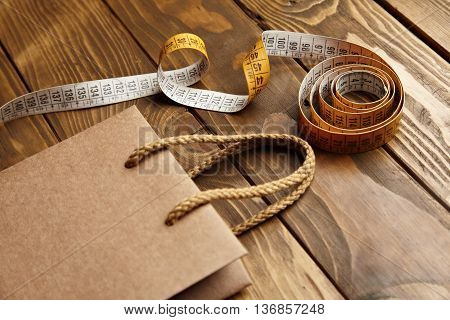 Brown takeaway bag from thic recycled craft paper on rustic wooden table near vintage tailoring meter close view mockup