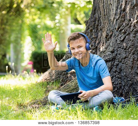 Outdoor portrait of happy teen boy 12-14 year old in headphones with tablet. Schoolboy watching media content in a tablet at park.