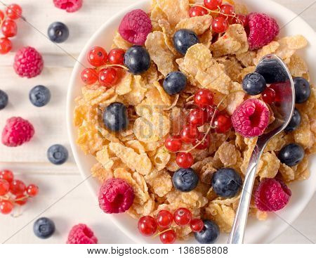 Cereal with berry fruit in the bowl from above.Selective focus on the corn flakes in bowl