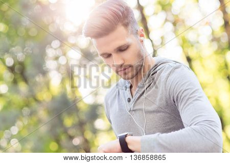Young sportsman is looking at his smart watch with seriousness. He is standing outdoors and wearing earphones