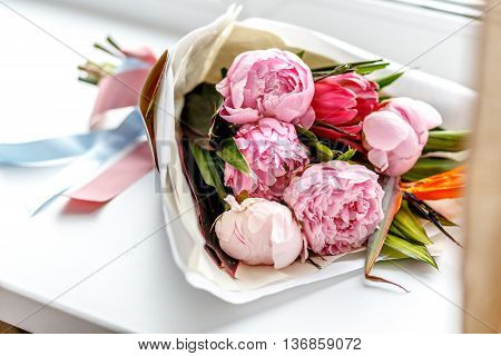Bouquet of pink peonies in kraft paper on white windowsill - gift for girl