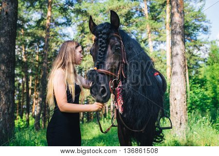 Young beautiful girl with a horse in woodland.