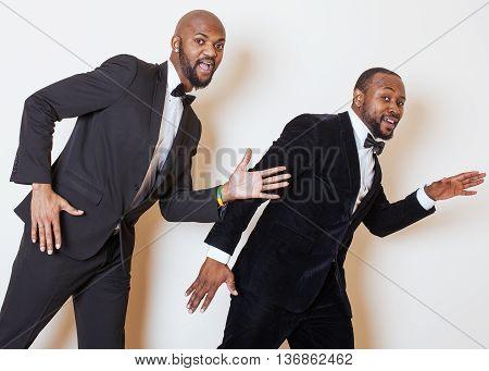 two afro-american businessmen in black suits emotional posing, gesturing, smiling. wearing bow-ties joking